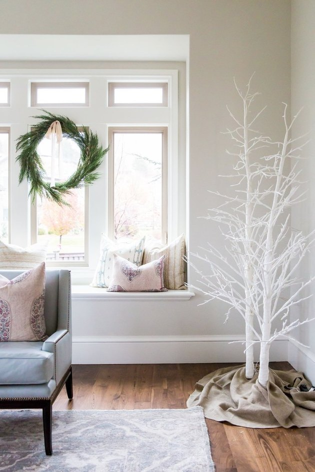 White Christmas Tree Ideas with White painted tree branches, window seat, evergreen wreath hung in window.