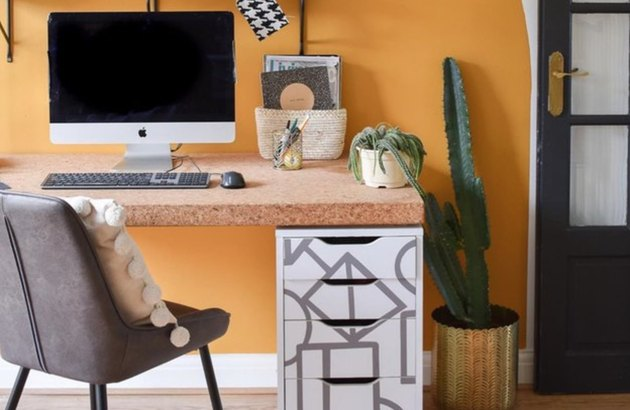 Home Office Paint Colors with Orange wall with desk and chair, computer screen, cactus.