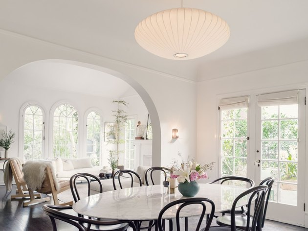 white living and dining room with table, and arched windows