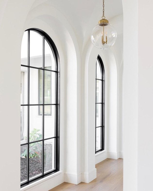 white hallway with black paned arched windows