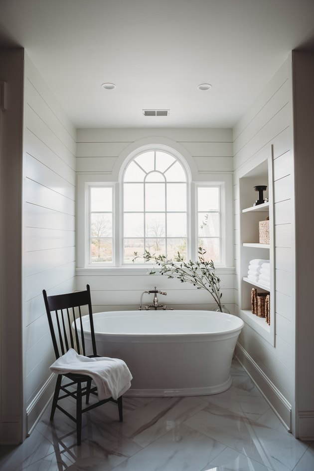 white bathroom with tub and arched window