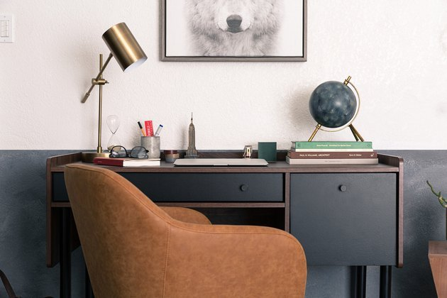Home Office Paint Colors with Brown desk chair, black desk, half black half white wall, brass desk lamp, globe.