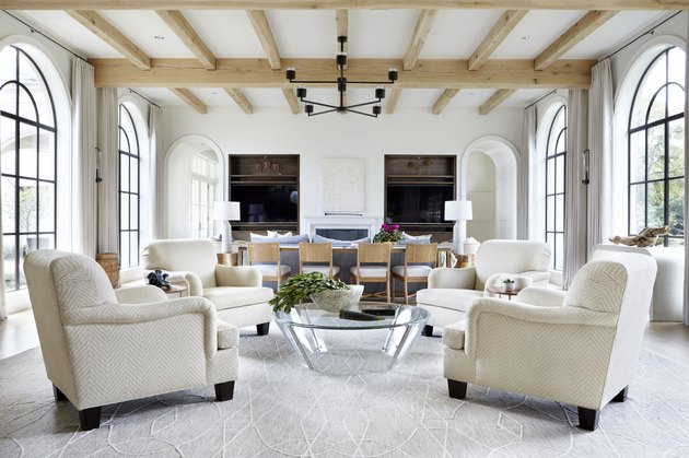 white living room with arched windows and wooden beams on ceiling