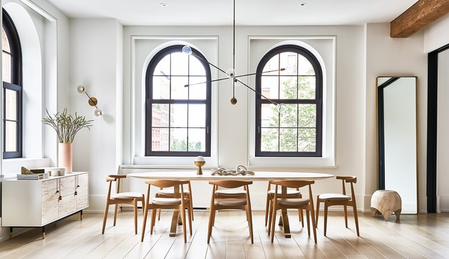 white dining room with arched windows and dining table