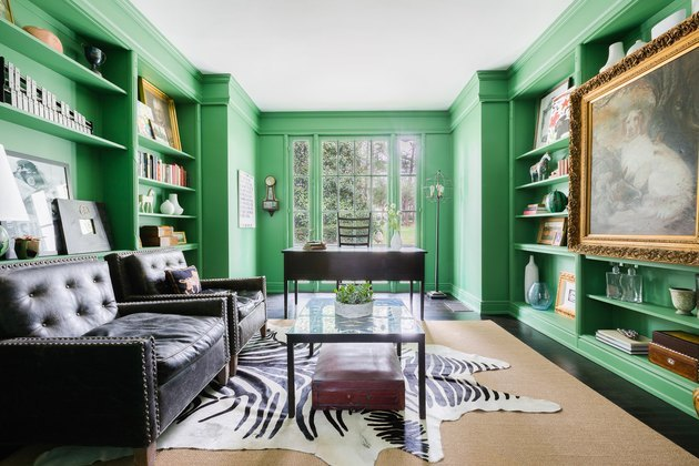 Home Office Paint Colors with Bright green walls with built in shelves, black leather couches, zebra print rug, coffee table, desk, books.