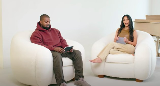 Kanye West and Kim Kardashian-West sitting in white chairs with piano in the background