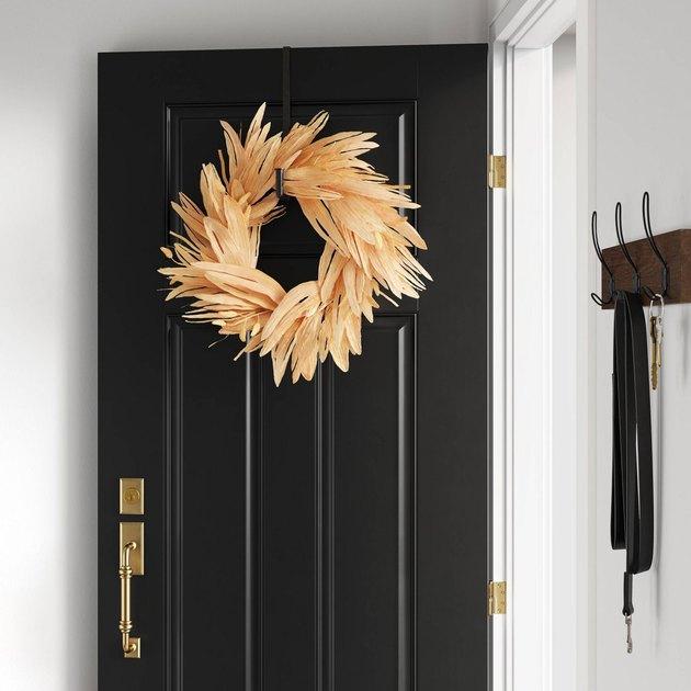 black door with artificial corn husk wreath