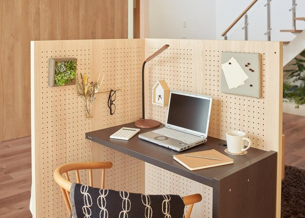 Panasonic's The Komoru at-home cubicle with a desk featuring a laptop, mug, and notepads