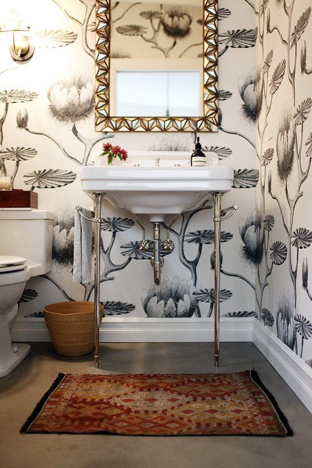 bathroom idea with console sink and patterned wallpaper with decorative mirror