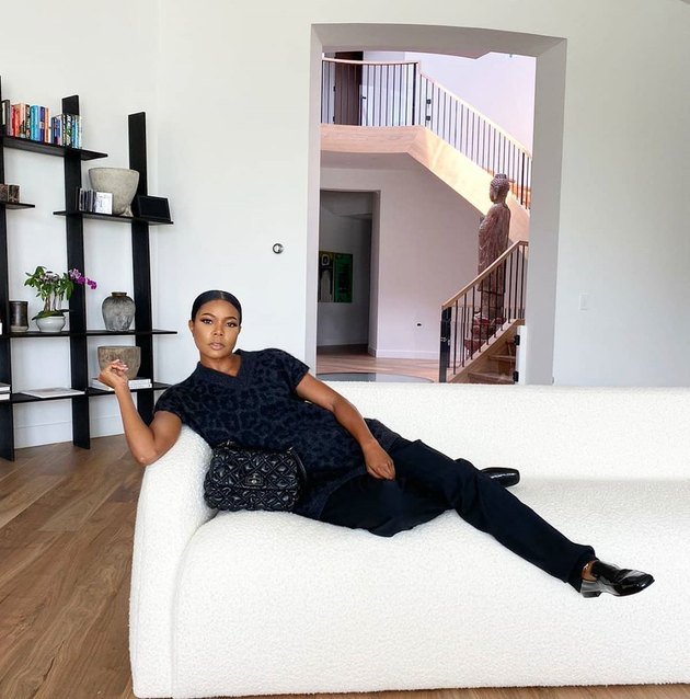 Gabrielle Union-Wade on white couch with black shelves in background