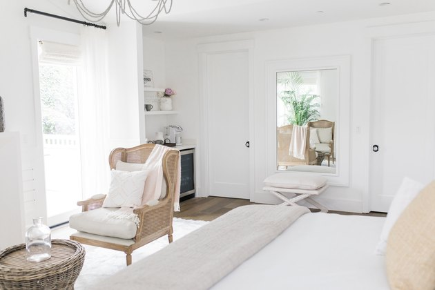white farmhouse bedroom with wingback lounge chair seating area