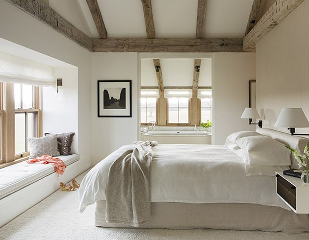 minimalist farmhouse bedroom with window seat and ceiling beams