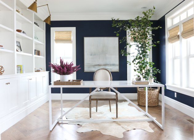 Home Office Paint Colors with White desk, white shelves, wood floor, navy accent walls, plant, flowers, vase and brass lamps.