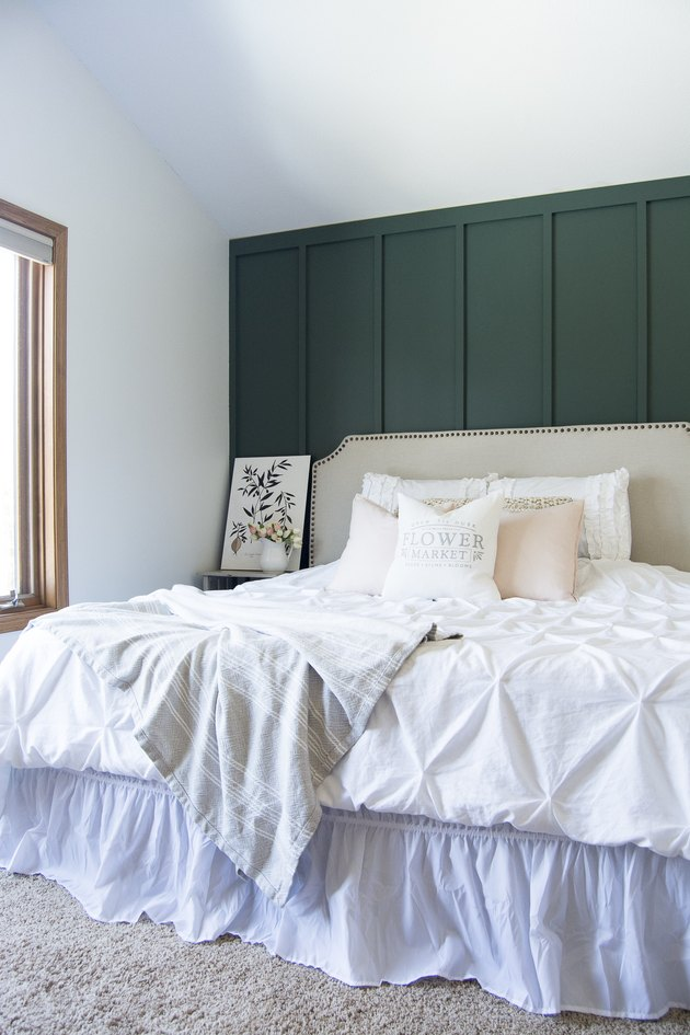 farmhouse bedroom with dark green board and batten accent wall