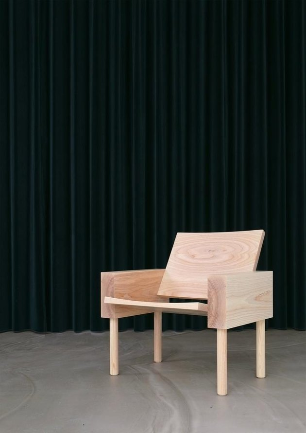 wooden chair on concrete floor with dark curtain in the background