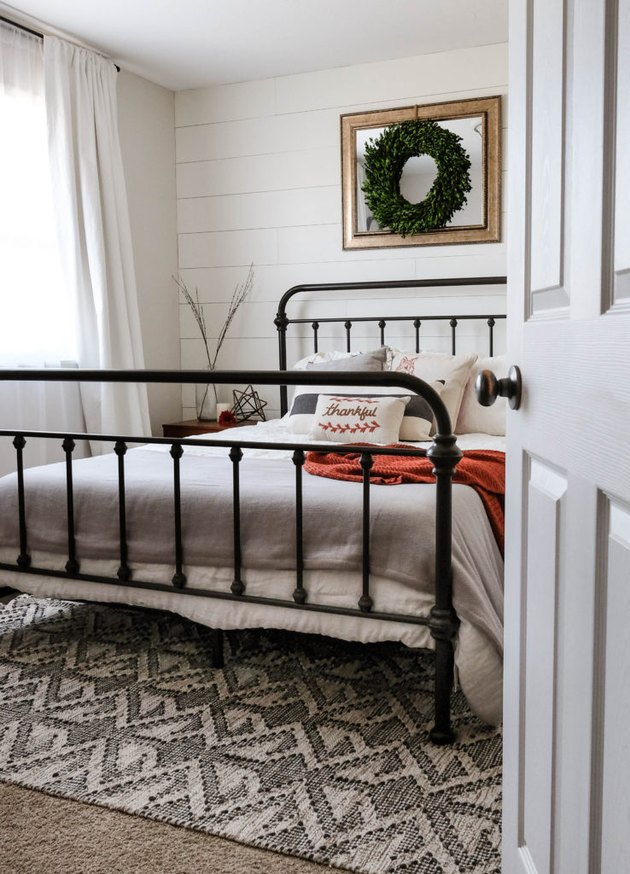 farmhouse bedroom with shiplap accent wall and iron bed frame