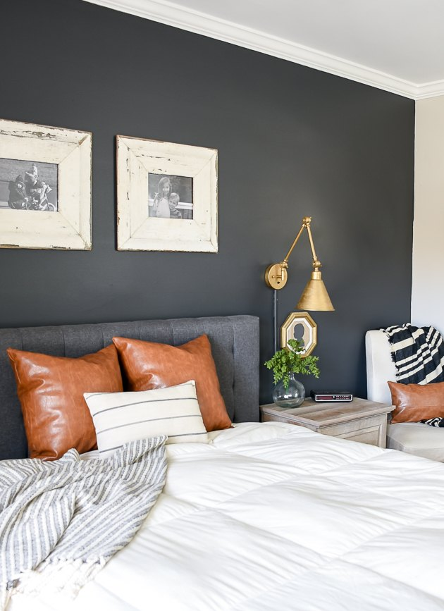 farmhouse bedroom with dark gray accent wall and brass wall sconces