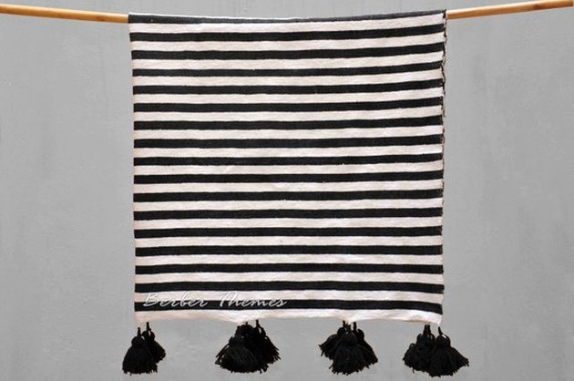 Black-and-white-striped throw blanket with black pom-poms on two sides