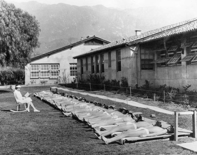 row of sunbathing young boys in California