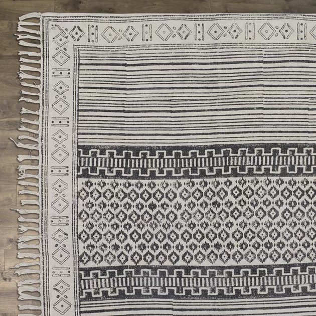 Gray are rug with short fringe and subtle stripes with geometric designs
