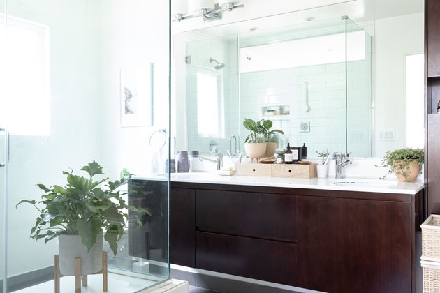 shower and double bathroom vanity with dark wood cabinets