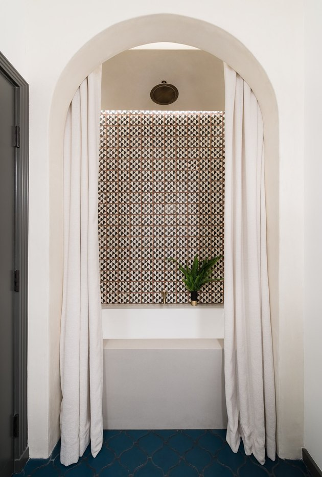 white bathroom color with patterned backsplash, arch and navy blue floors