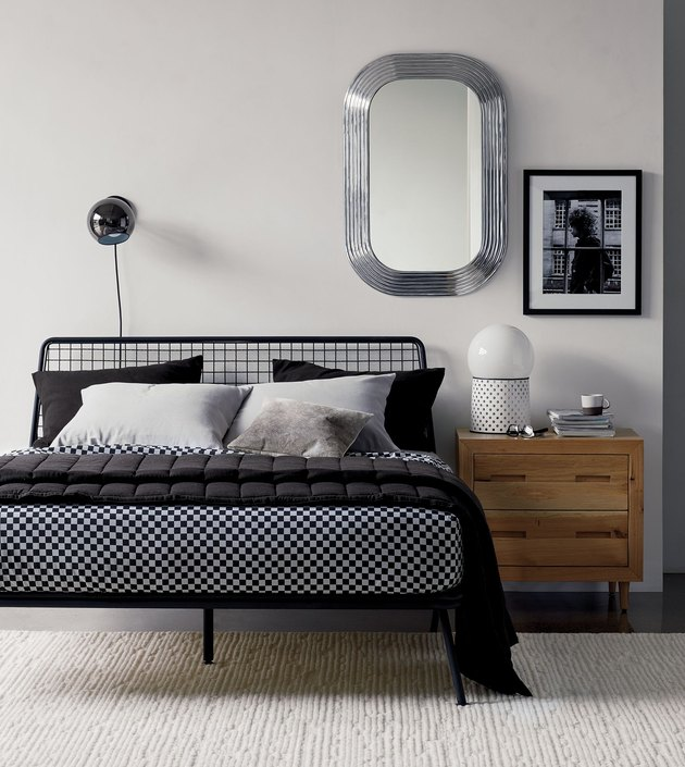 CB2 x GQ bedding on bed with wood nightstand and wall sconce