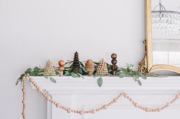 mini wooden holiday scene set on a mantel