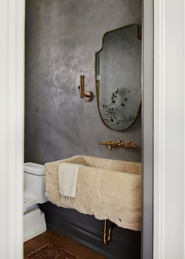 gray bathroom color with concrete sink and brass mirror