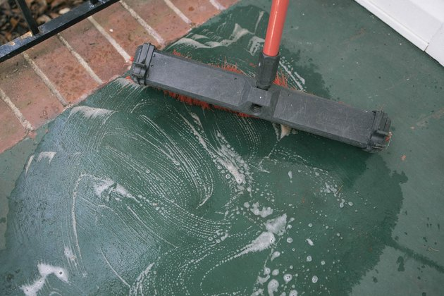 Cleaning concrete porch with degreaser and broom