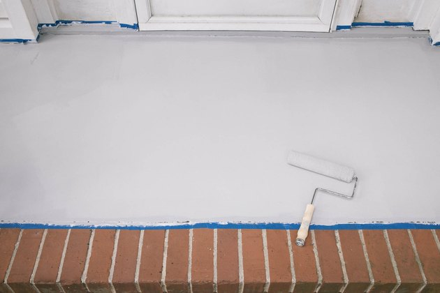 Rolling gray paint onto the concrete porch