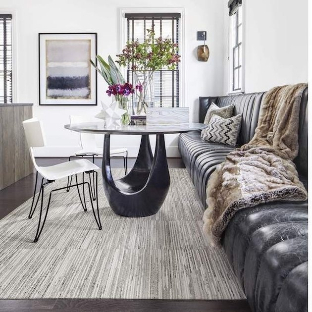 dining room rug idea with carpet tile beneath sculptural table and channel-tufted bench
