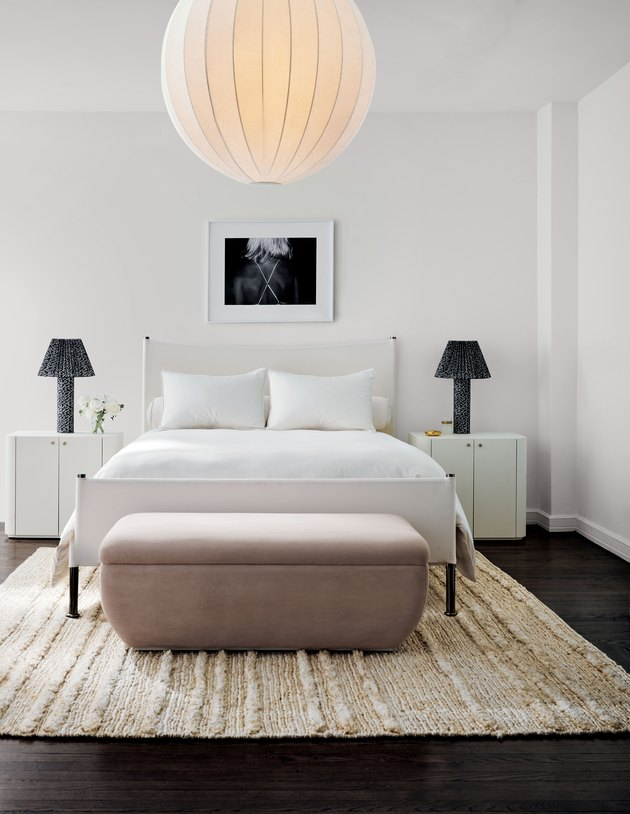 bedroom with white bedding, blush bench, and black table lamps