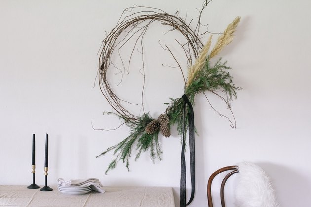 Rustic winter wreath with pampas grass and greens hanging on wall over table.