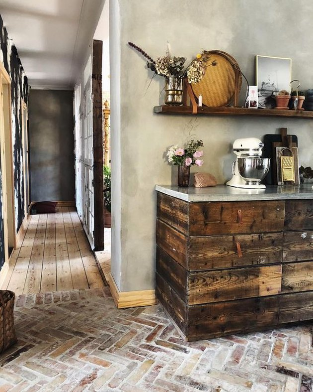 rustic kitchen with herringbone pattern flooring and wood cabinets