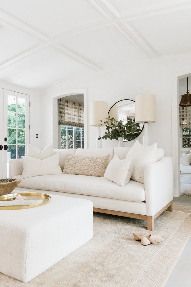 white living room with plush sofa and ottoman