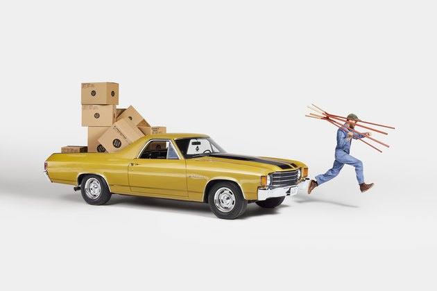 gold chevrolet el camino with boxes and man running away with coat rack