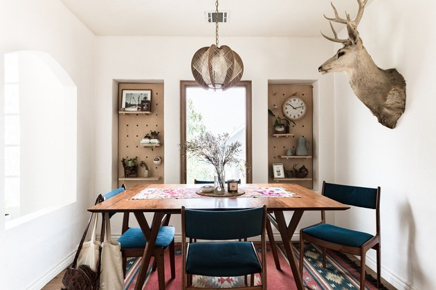 dining room area with animal head and pegboard storage