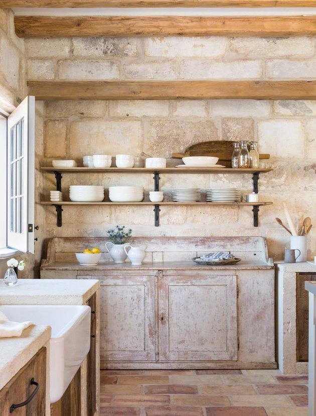 country kitchen with brick flooring and walls and weathered cabinetry