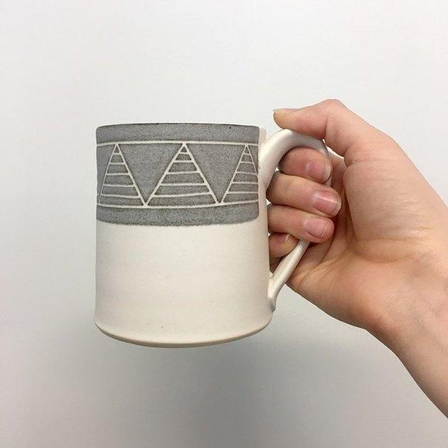 handmade ceramic mug with hand-carved design