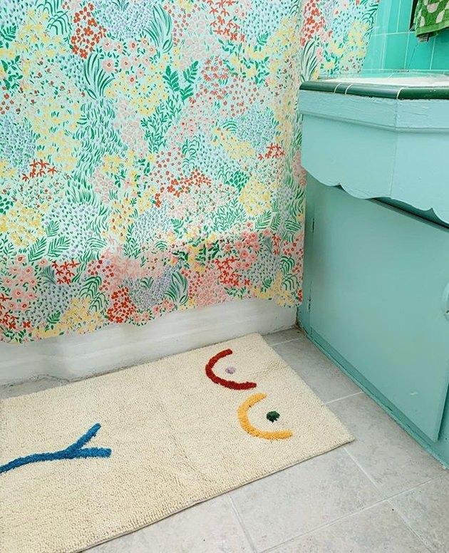 teal bathroom with cream bath mat