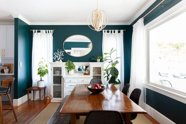 A bright green dining room with white curtains