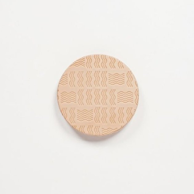 vegetable tanned leather coaster with embossed design
