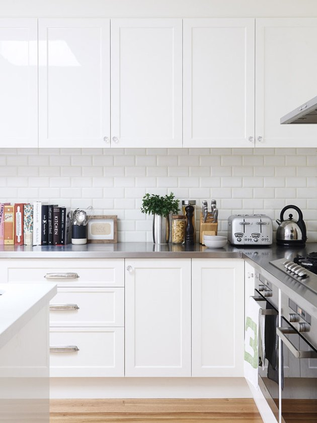 white kitchen with stainless steel countertops and appliances