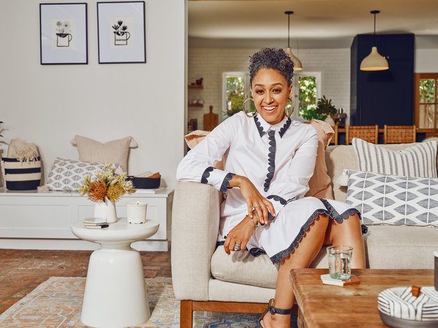 Tia Mowry sitting on couch near white side table