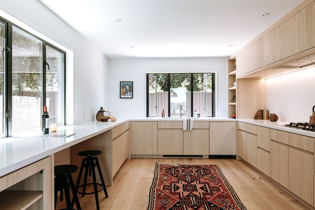 Wood kitchen cabinets with boho rug in center of kitchen