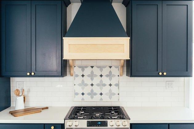 Kitchen with blue cabinets, white tile backsplash, and patterned tile behind stove