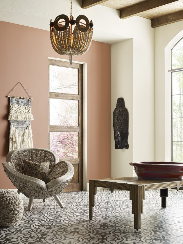 room with table, chair, and wall hanging with peach-colored wall
