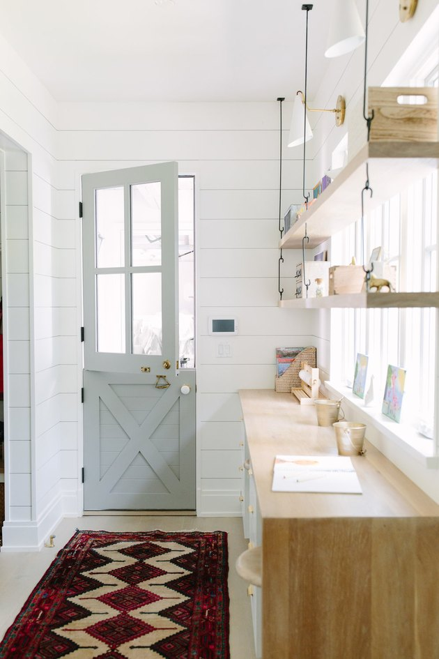 shelving with tchotchkes and Dutch style door with shiplap walls