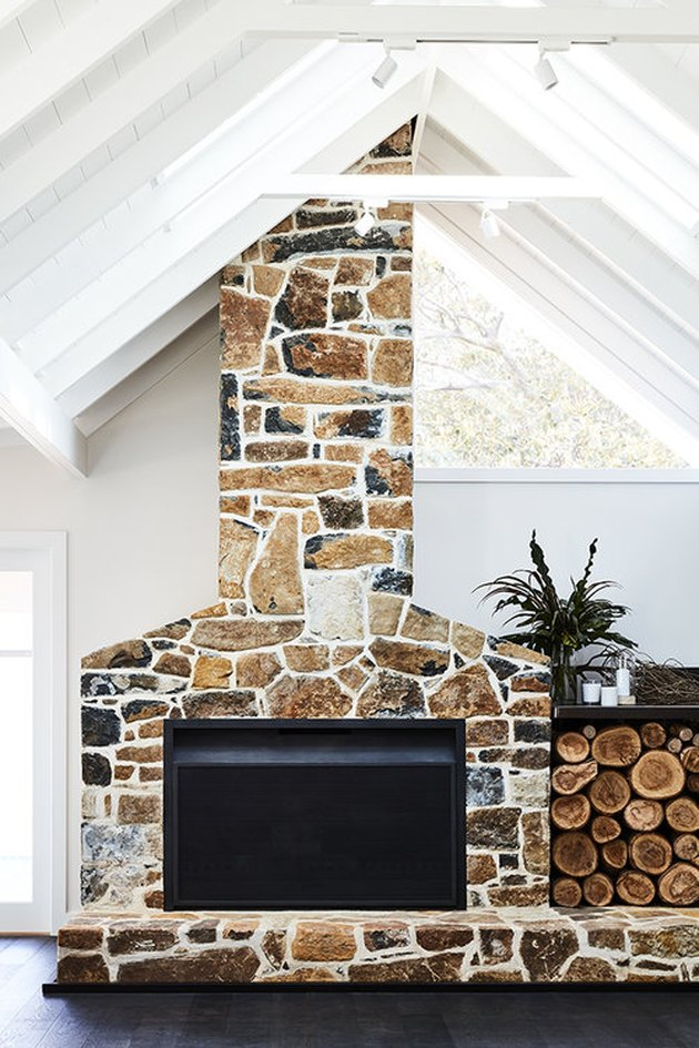 stone fireplace with stacked wood and A-frame ceiling